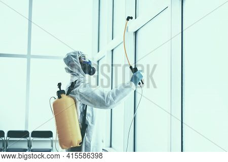 Disinfector In A Protective Suit Is Spraying A Disinfectant In The Room.