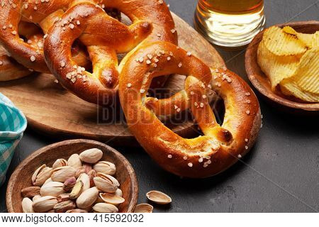Lager beer mug, nuts, potato chips and fresh baked homemade pretzel with sea salt. Classic beer snack