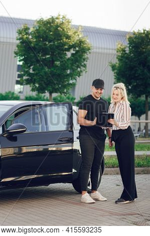 Happy Young Man Signs Documents To Buy A New Car. Female Salesman Shows The Buyer A New Car. Test Dr