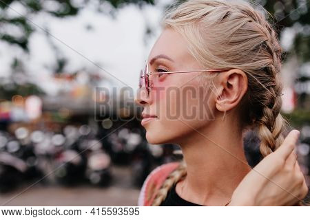 Adorable Blonde Woman In Sunglasses Touching Her Braids. Outdoor Close-up Shot Of Pretty Fair-haired