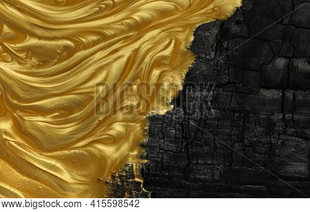 Vivid contrast of black and gold in abstract background of metallic gold paint swirling over charred black ashes.