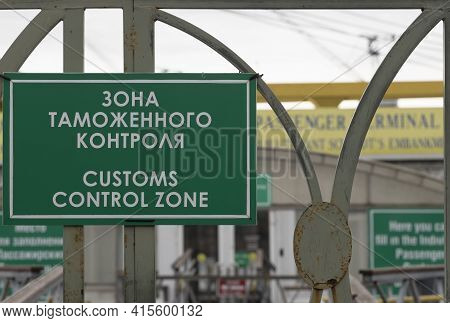 Green Sign With The Inscription In Russian And English 'customs Control Zone' On The Grid Above The