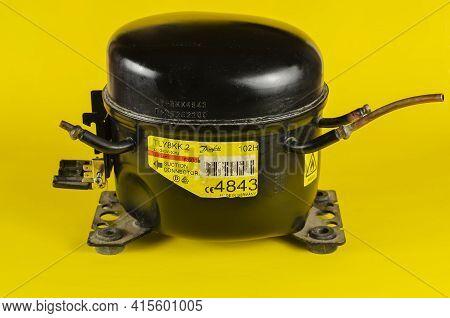 Black Refrigerator Compressor On Yellow Background. Old Hermetic Piston Compressor. Device Designed