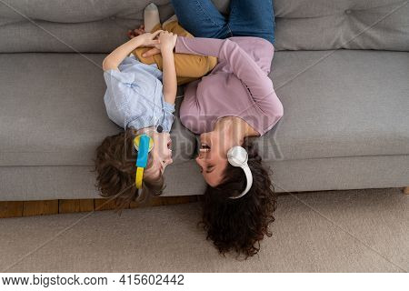 Smiling Happy Mother And Kid Son Lying Upside Down On Couch At Home, Laughing, Tickle Each Other, He