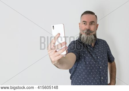 Bearded Hipster Style With Caucasian Appearance 40-45 Years Old Using The Smart-phone To Take A Self