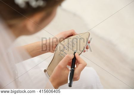 Young Bride Writing Her Single Friends Names On Shoe Indoors, Above View. Wedding Superstition
