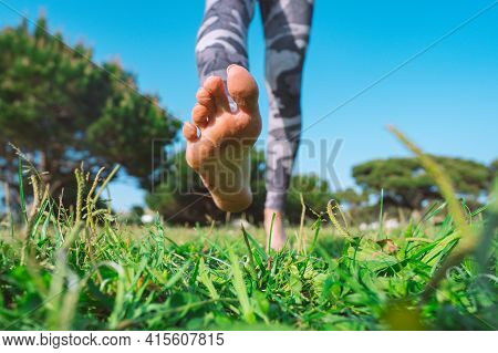 Closeup Of Woman Walking Barefoot On The Green Grass. Barefoot Running In The Park