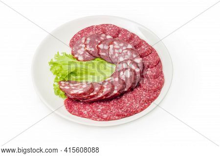 Sliced Dry-cured And Smoked Sausages Lie On Lettuce Leaf On White Dish On A White Background