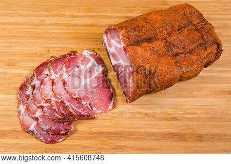 Piece And Several Slices Of Dry-cured Pork Neck In Paprika And Chili Powder Mix On A Wooden Cutting