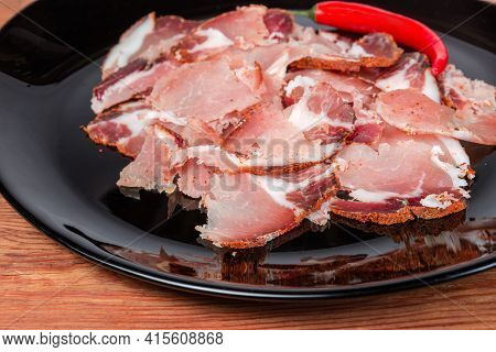 Thin Slices Of Dry-cured Pork Neck On Black Dish, Fragment Close-up In Selective Focus