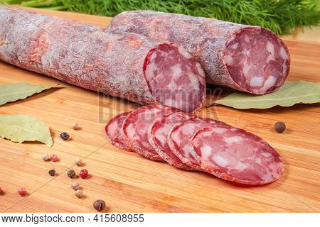 Partly Sliced Dry-cured Sausage Among Some Spices On The Wooden Cutting Board, Close-up In Selective