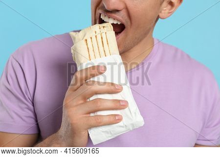 Man Eating Delicious Shawarma On Turquoise Background, Closeup