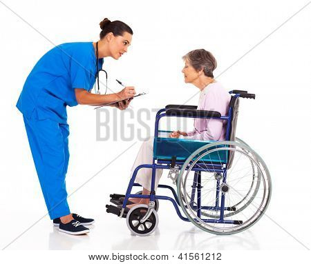 caring nurse helping senior patient filling medical form