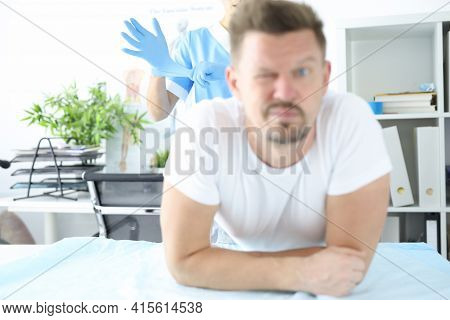 Doctor Putting On Protective Glove For Rectal Examination Of Man