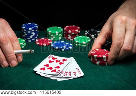 Hands Of A Gambler Closeup And Chips On Green Table In A Poker Club. A Player Places A Bet On Winnin