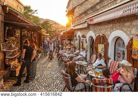 Mostar, Bosnia and Herzegovina - August 30, 2019: Cobbled street with cafes and souvenir shops in old town of Mostar