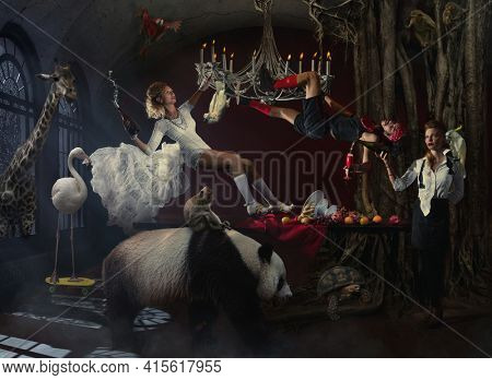 Crazy punk wedding surrounded by animals and trees. The bride and groom hung on the chandelier and the waitress pours champagne to the groom