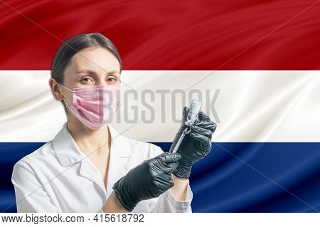 Girl Doctor Prepares Vaccination Against The Background Of The Netherlands Flag. Vaccination Concept
