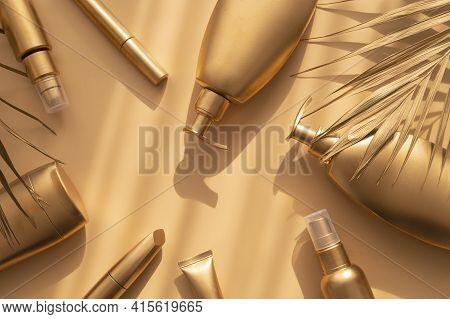 Golden Clean Bottles Of Cosmetics, Palm Gold Leaf On Beige Background. Cosmetic Mock Up Bottles, Tub