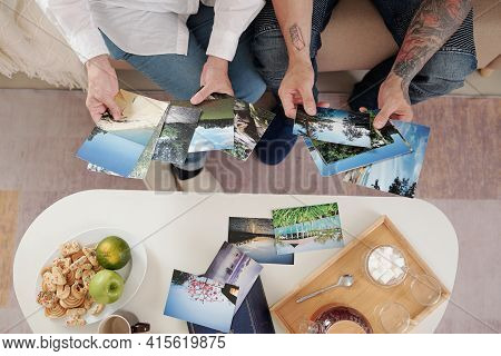 Hands Of Mother And Adult Son Drinking Tea With Sugar Cookies And Looking At Printed Old Photos Of N