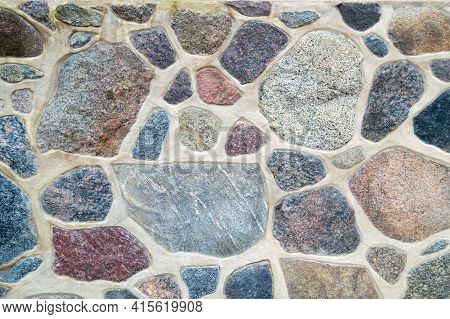 Wall Made Of Natural Stone And Cement. Fragment Of A Colored, Textured Stonewall. Bright Background.