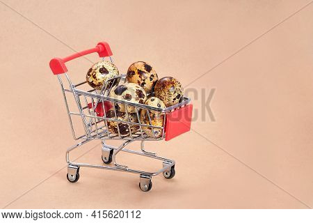 Quail Eggs In A Supermarket Cart. Close-up Of Quail Eggs In A Shopping Basket On A Beige Background.