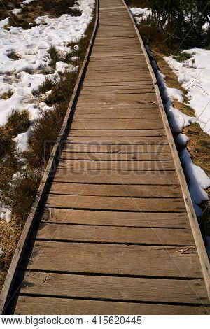A Beautiful Wooden Footbridge In The High Moor With Snow In Spring