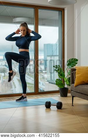 Slim brunette does exercise standing on right leg with hands behind head at panoramic window with city view on glazed balcony
