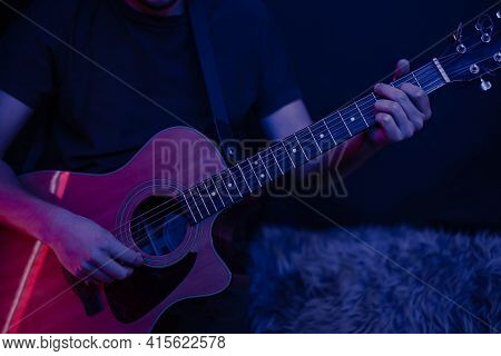 A Man Plays An Acoustic Guitar In A Dark Room Copy Space. Live Performance, Acoustic Concert.