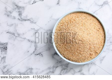 Fresh Breadcrumbs In Bowl On White Marble Table, Top View. Space For Text