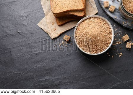 Fresh Breadcrumbs On Black Table, Flat Lay. Space For Text