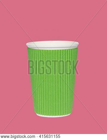 Photo of an green paper cup on a colored pink background. Photo of a coffee cup made of recyclable materials. Empty paper coffee cup.