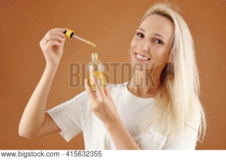 Portrait Of Happy Young Pretty Woman Showing Bottle Of Serum Or Oil For Hair Moisturizing And Condit