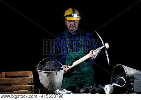 A Miner With A Pickaxe In His Hand Stands By A Bucket Full Of Black Coal On A Black Background
