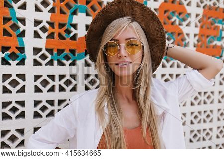 Magnificent Fair-haired Woman Touching Her Brown Hat While Posing At Summer Resort. Adorable Girl Wi