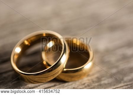 Two golden wedding rings on wooden background