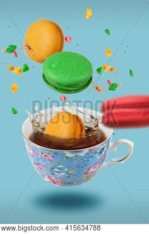 Color French Macaroons Falling In To The Decorated Blue Porcelain Teacup Full Of Tea, Selective Focu