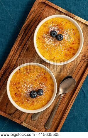 Creme Brulee In Ramekin On Wooden Tray On Dark Linen Tablecloth. Close Up French Vanilla Cream Desse