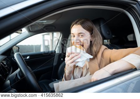 Happy Woman Eating A Burger In The Car. Bites A Sandwich. Have Unhealthy Fast Food Snack. Food To Go