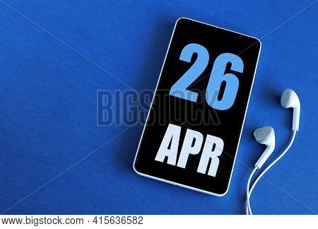 April 26. 26 St Day Of The Month, Calendar Date. Smartphone And White Headphones On A Blue Backgroun