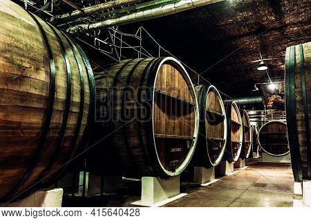 Old Barrels In The Wine Cellar. Wine Cellar With Old Oak Barrels, Production Of Fortified Dry Or Sem