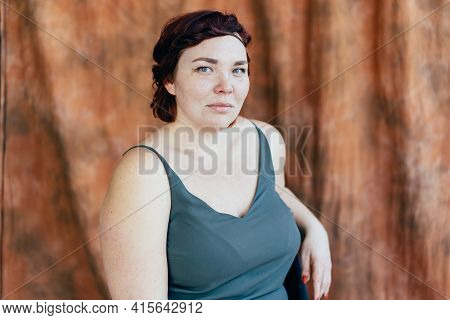 Portrait Of A Freckled Plus Size Woman. Studio Portrait Over Brown Fabric Background. Simple Natural
