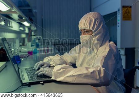Scientist in protective workwear and mask typing on laptop at her workplace she working till late night in the lab