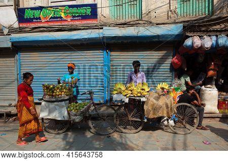 Kathmandu, Nepal - June 19, 2019: Fruit sellers on bicycle sell bananas and mango on Kathmandu street. Old nepali woman walking in red traditional clothes, street vendors