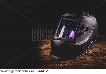 Black Welding Mask On A Wooden Background. A Studio Photo With Hard Lighting.