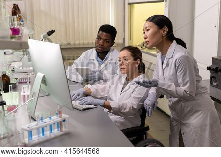 Group of scientists sitting at the table looking at computer monitor and working on computer in team in the laboratory