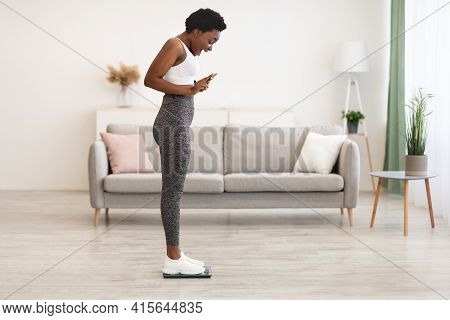 Joyful African Lady Weighing Herself After Diet On Weight-scales Indoor