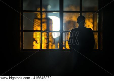 The Silhouette Of A Man With Arms Crossed In Front Of A Window With A View Over A City Lit In The Ni