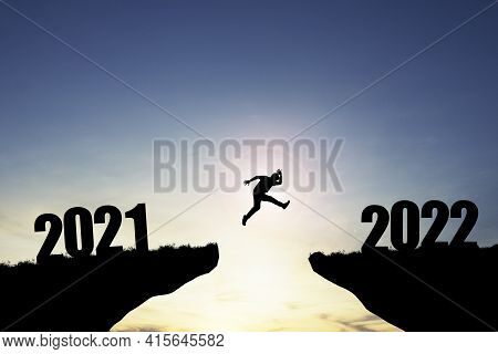 Silhouette Man Jumping From 2021 Cliff To 2022 Cliff With Blue Sky And Sunlight, Preparation New Cha