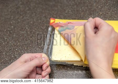 Opens A Bag Of Sliced Cheese, A Woman Opens A Bag Of Cheese, Pieces Of Cheese In A Bag. Cheese Packa